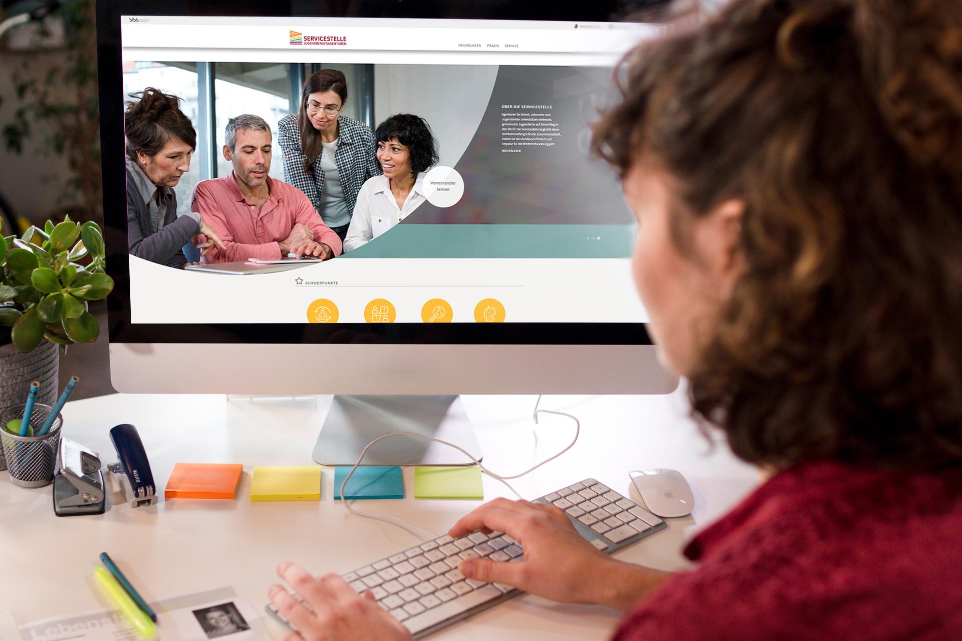 Eine Frau sitzt am Schreibtisch und bedient die Tastatur. Sie schaut auf den Bildschirm, auf welchem vier Mitarbeiter zusammen über etwas sprechen.