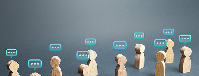 Menschenfiguren aus Holz mit Kommentarwolken über ihren Köpfen