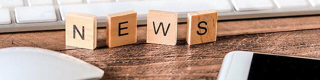 Schreibtisch mit Buchstaben News auf Holzstücken geschrieben.