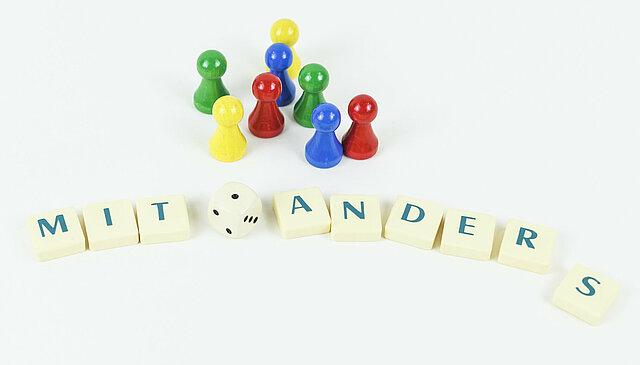 """Mit Hilfe von Scrabble-Spielsteinen auf die jeweils ein Buchstabe gedruckt ist, ist das Wort """"MITEINANDERS"""" gelegt. Eine Gruppe verschiedenfarbiger Spielfiguren und ein Würfel stehen darüber als Symbole für Vielfalt."""