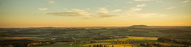 Blick auf das Erzgebirge bei Sonnenaufgang. Im Vordergrund der Pöhlberg.