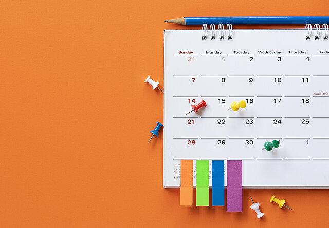 Tischkalender auf dem bunte Post-It's kleben und bunte Pinnwandnadeln verteilt sind, darüber liegt ein blauer Bleistift