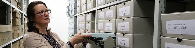 Eine Mitarbeiterin steht vor einem großen Regal voller Kartons. Sie hat einen Karton halb herausgezogen.