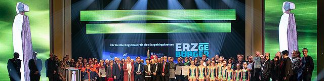 Zu sehen ist ein Bühnenbild zur Preisverleihung des ERZgeBÜRGER – dem Regionalpreis des Erzgebirges. Die Veranstaltung zeichnet ehrenamtlich Engagierte aus dem Erzgebigskreis aus. Im Hintergrund befindet sich ein LED-Leinwand vor der sich alle Preisträger sowie Vertreter aus Politik und Wirtschaft für ein gemeinsames Foto versammelt haben.
