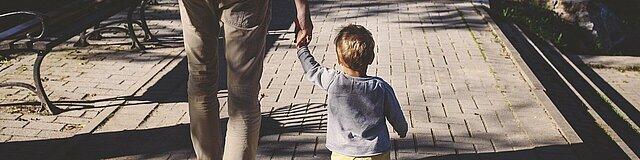 Ein Mann läuft mit einem Kleinkind den Fußweg entlang; Blick von hinten